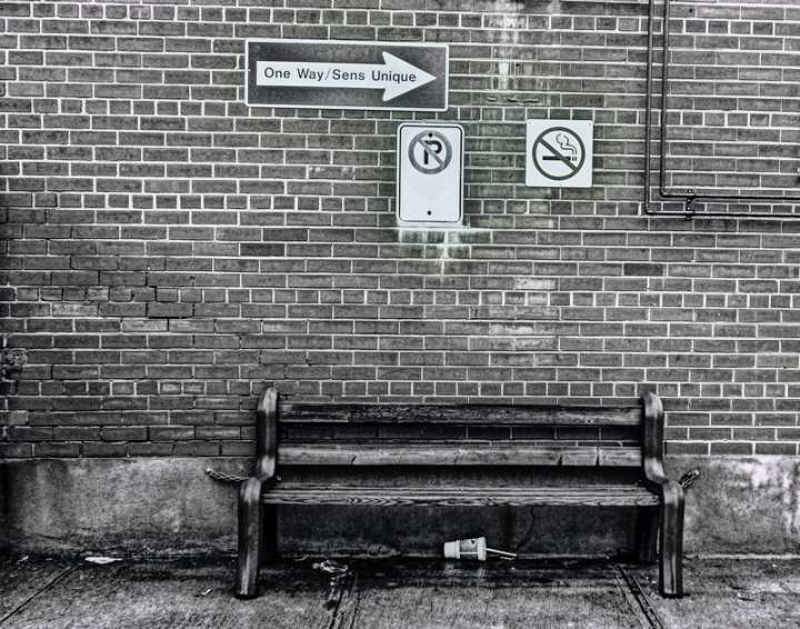 city bench with brick wall and signs